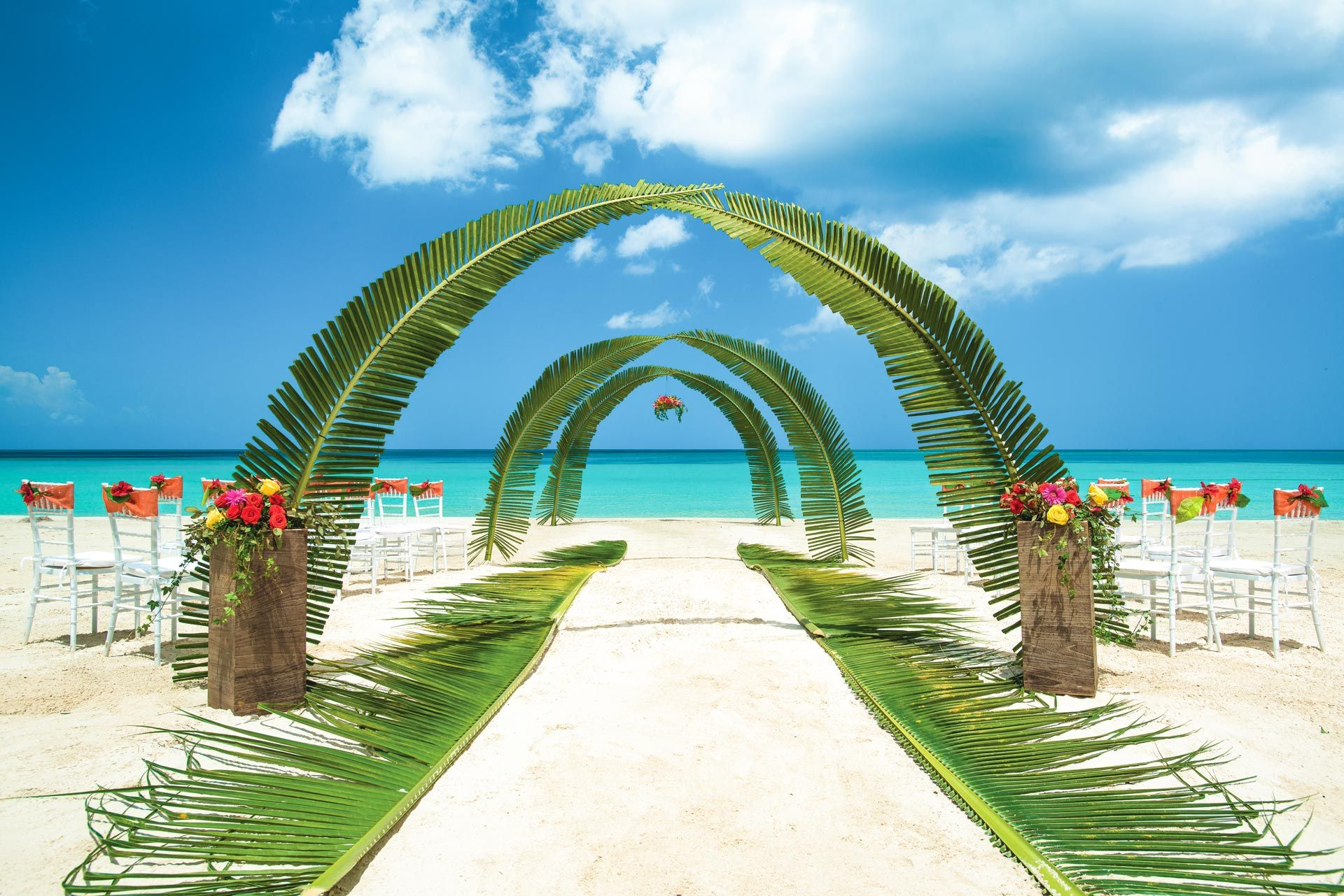 Beach wedding ceremony with palm leaves