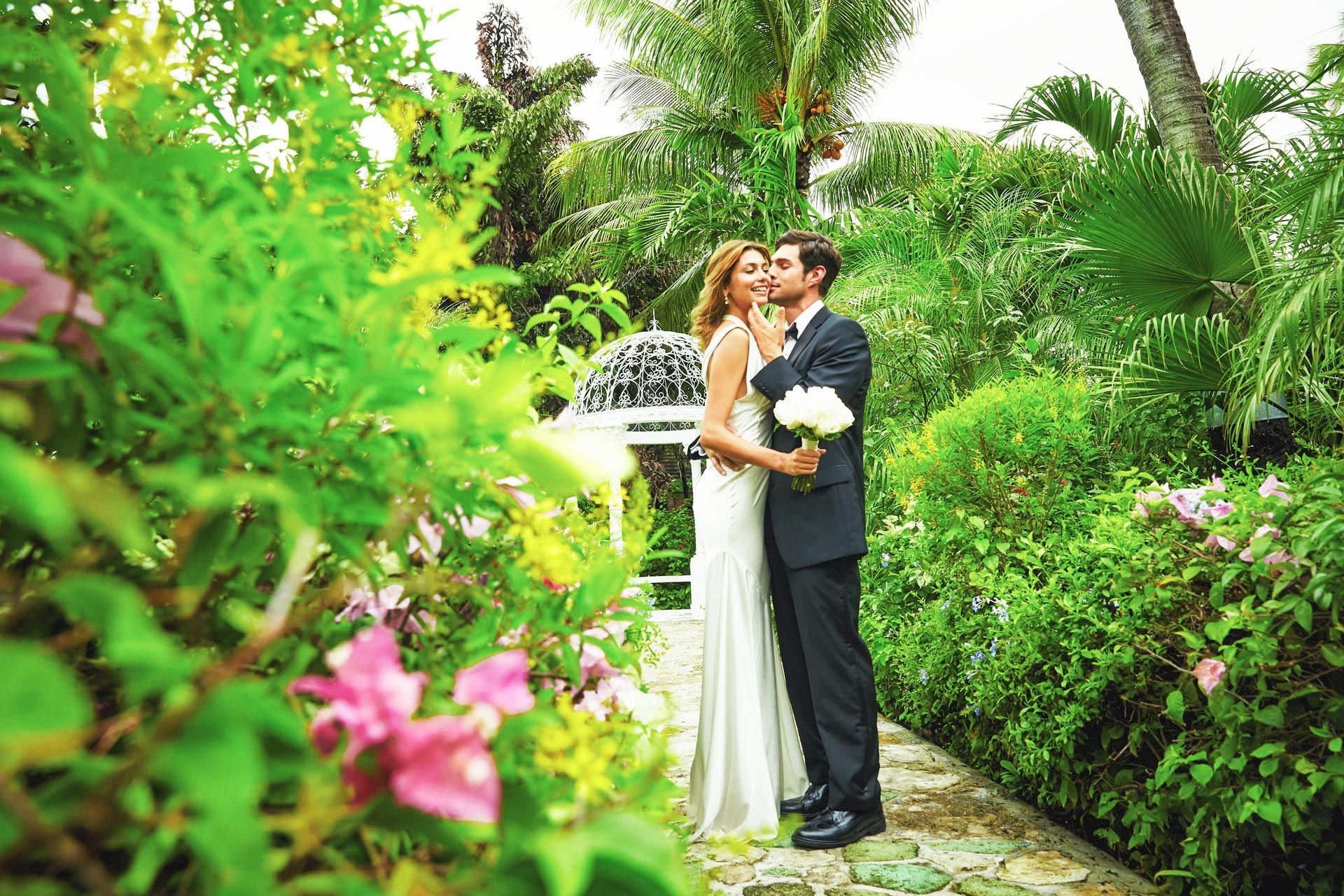 Wedding couple in gardens kissing