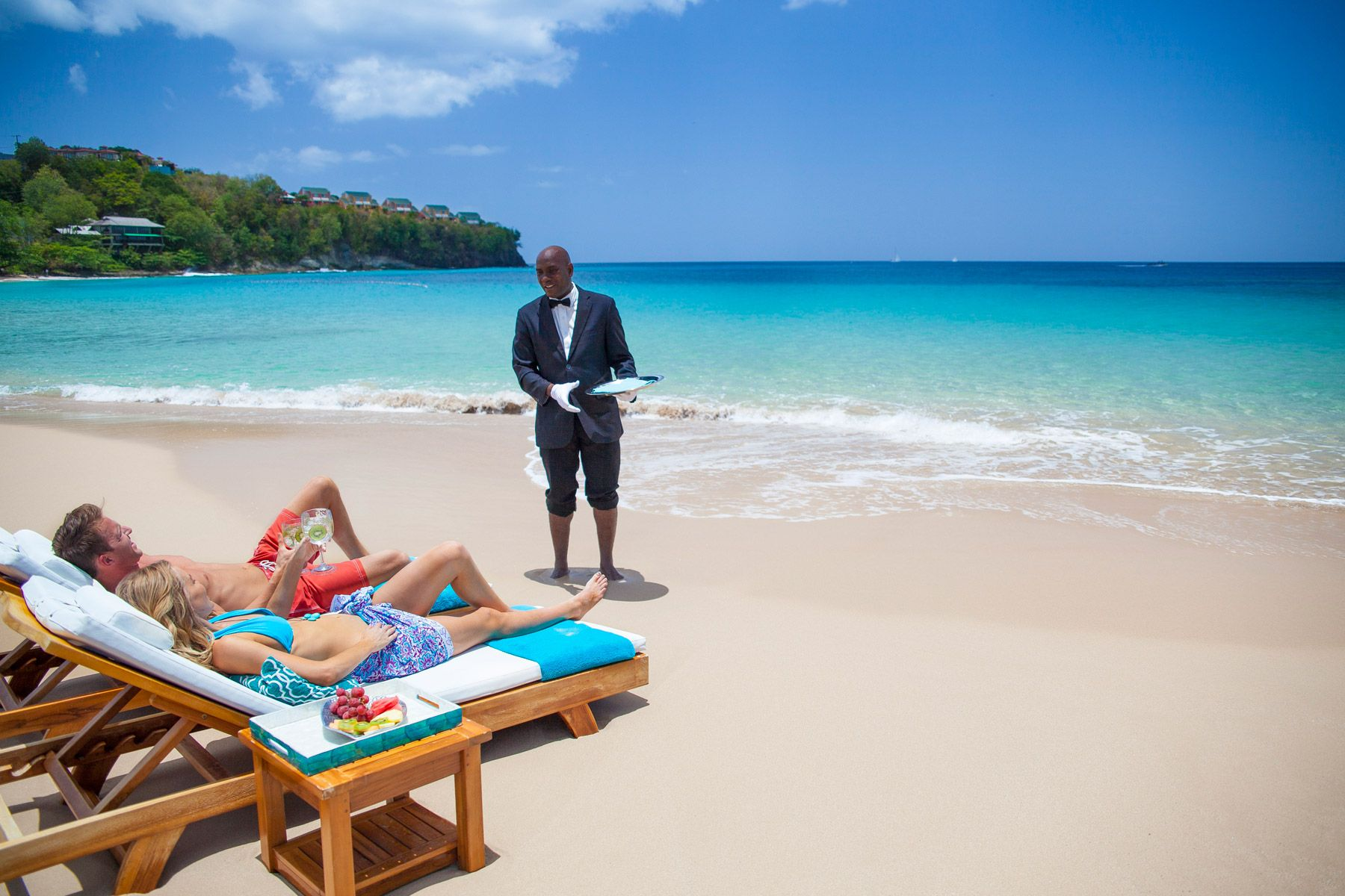 couple enjoying butler service at beach in sandals regency la toc