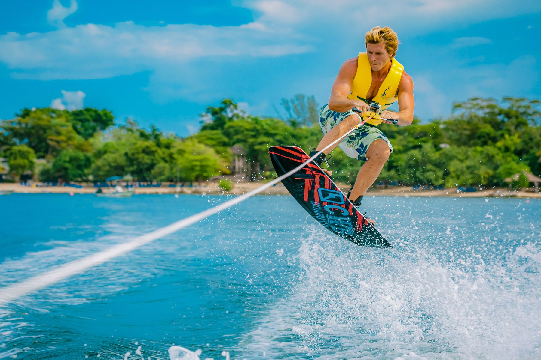young man wakeboarding and jumping wave
