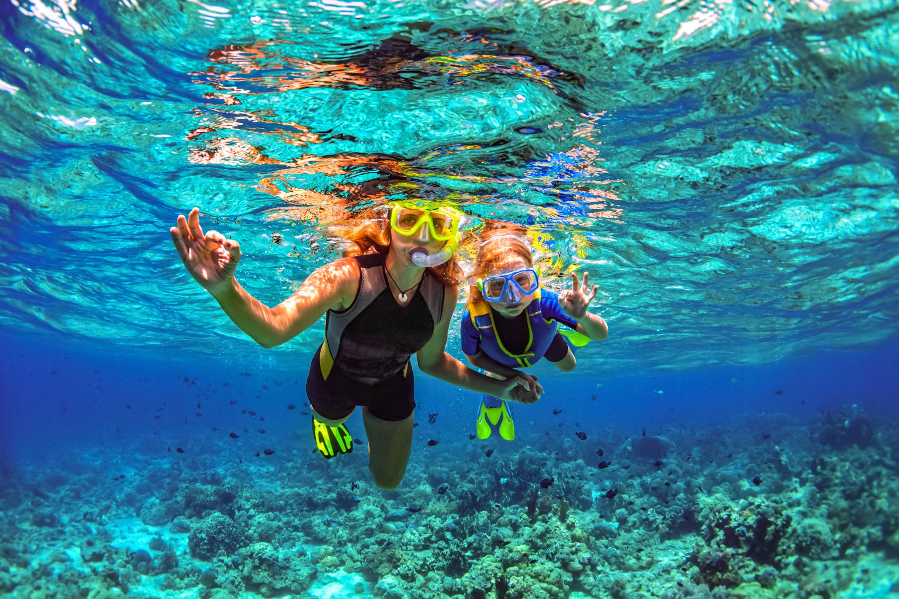 mother kid snorkeling coral reef