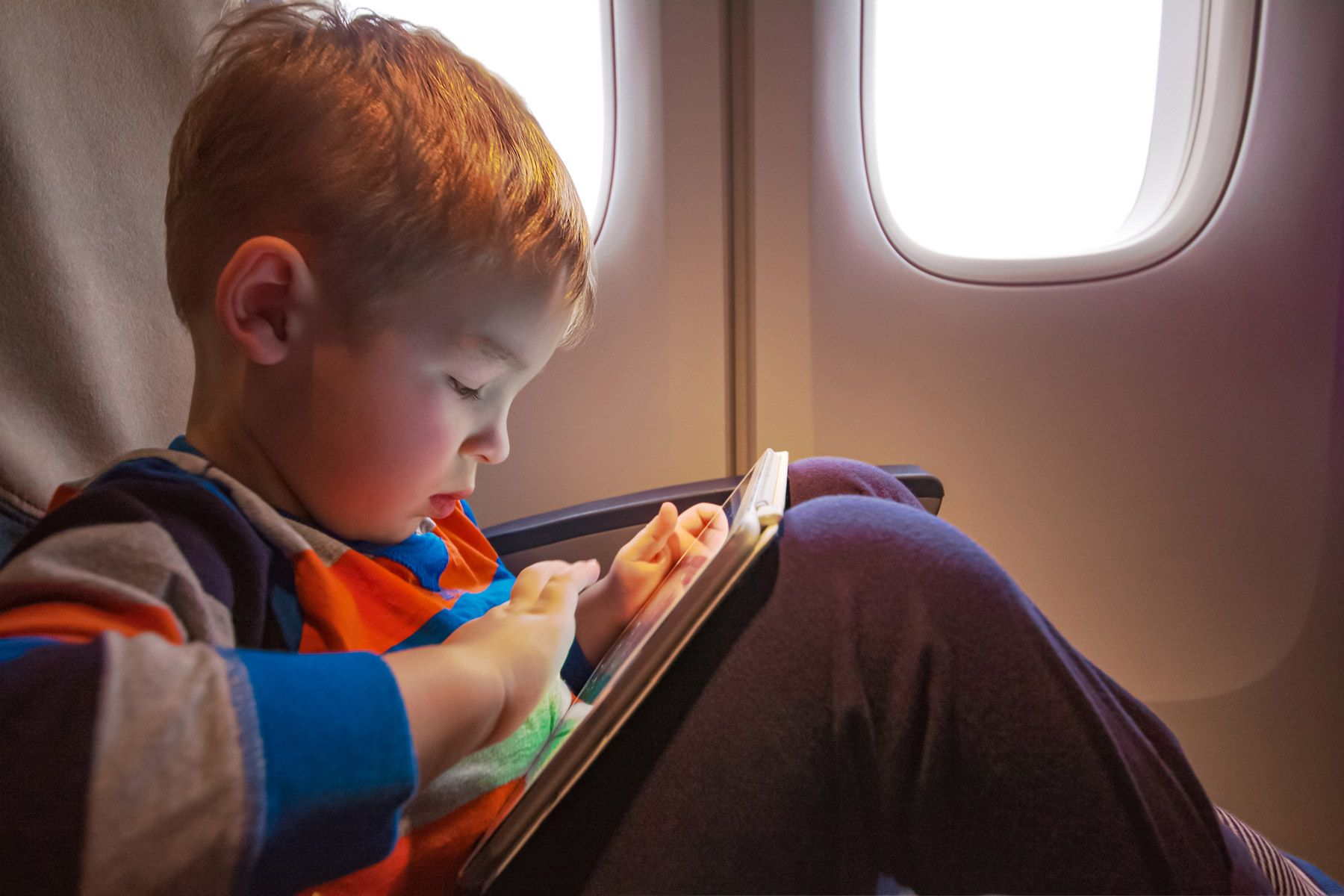 child with tablet plane