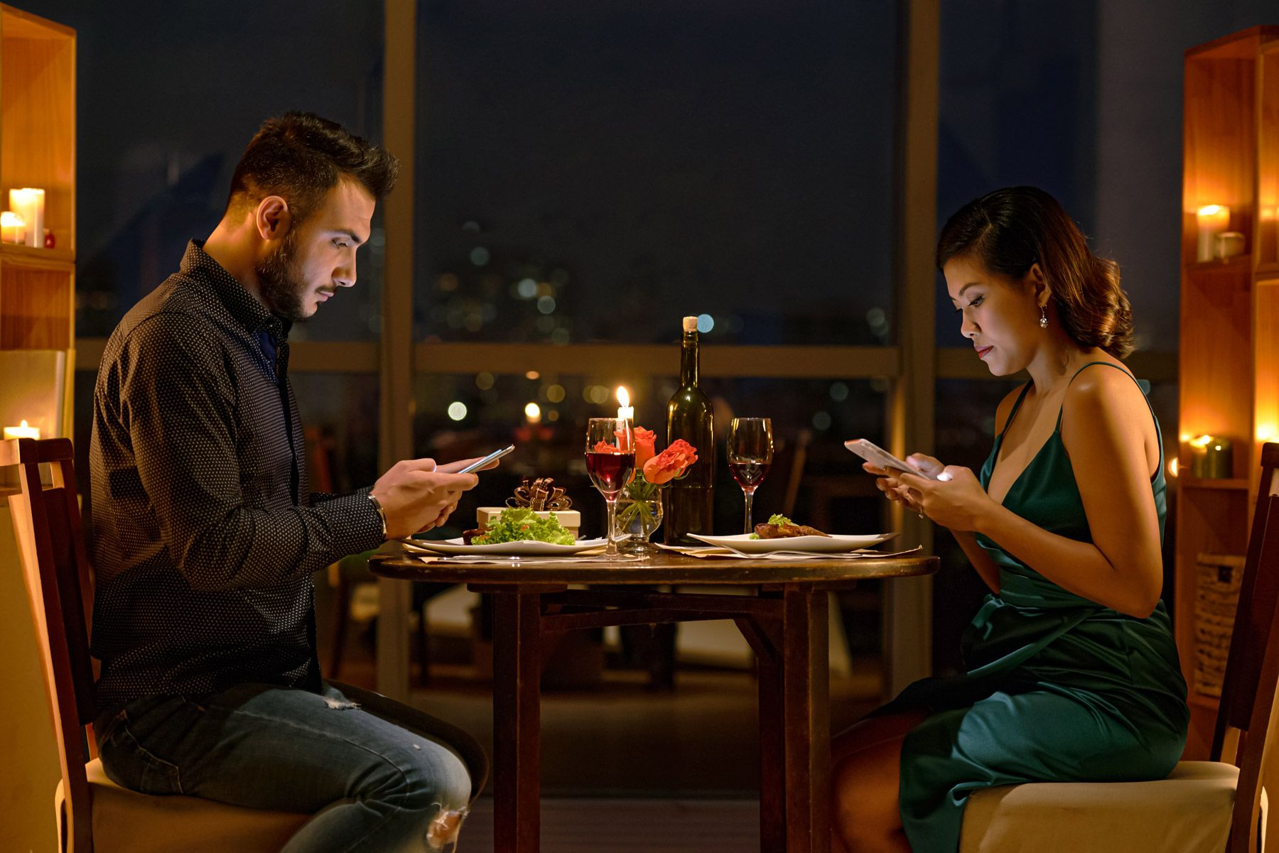 young couple using phones during date