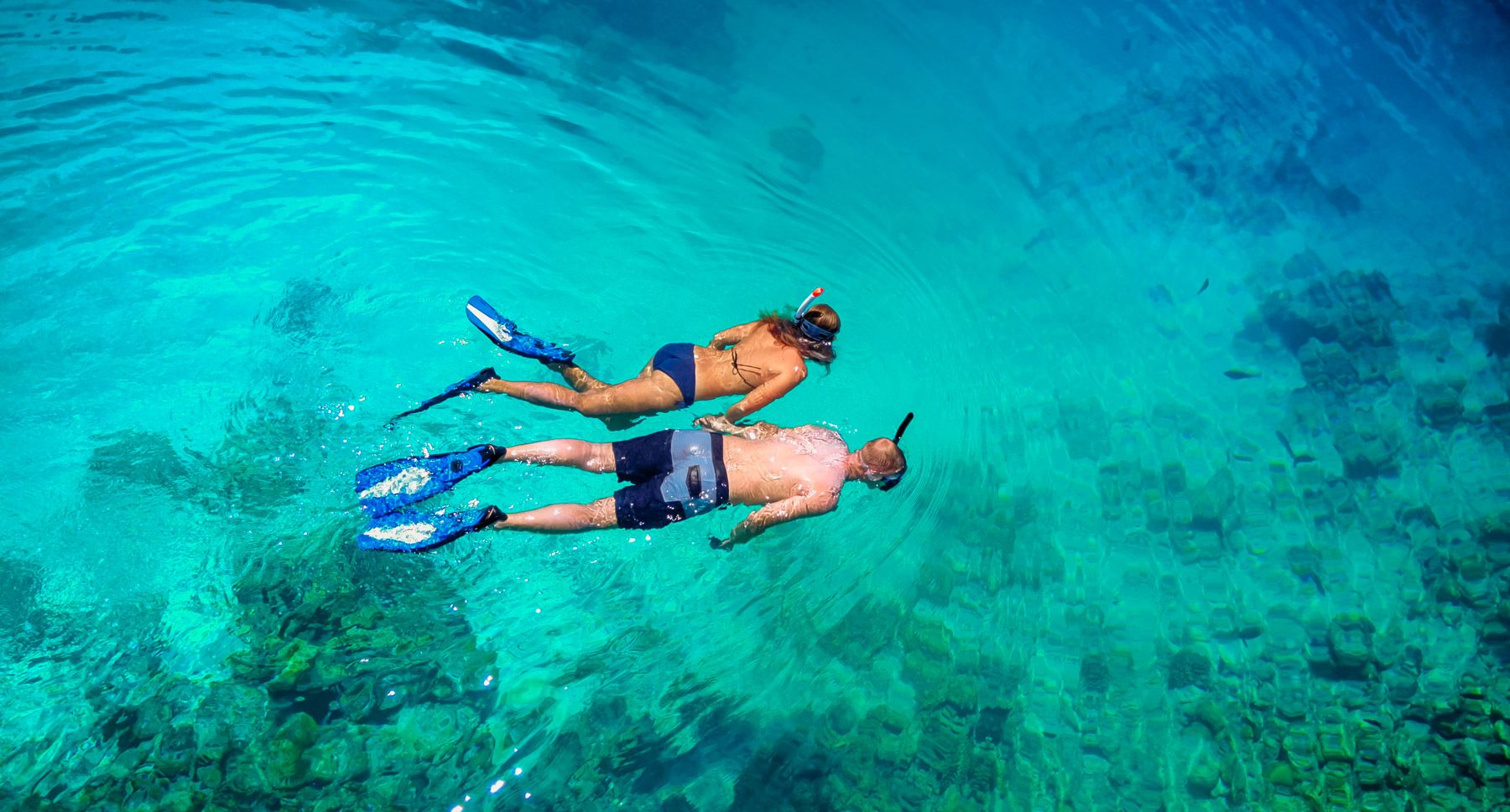 top view of couple snorkeling in clear tropical waters