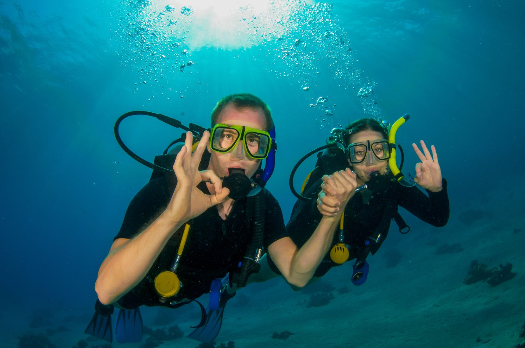 couple scuba diving giving the OK signal